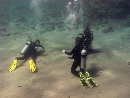 Drie duikers zitten op de Rode Zee onder zand en opleiding Stockfoto