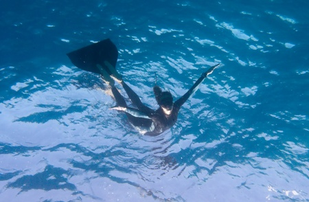Freediver looks like flying underwater from surface. Dahab, Egypt, Red Sea.