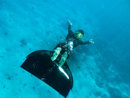Beautiful freediver girl swims above sea bottom sand and corals in Dahab, Egypt
