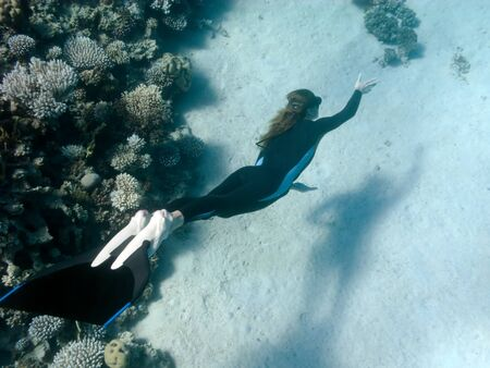 Beautiful girl with monofin swims near coral reef in Dahab, Egypt