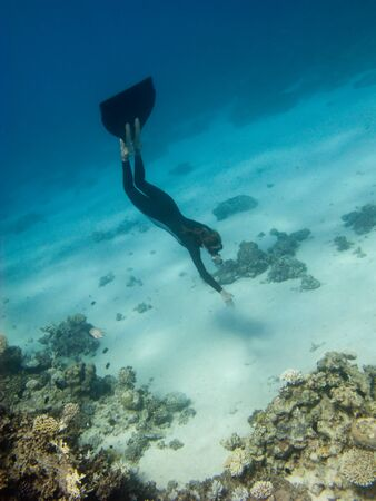 Freediver girl dives toward sand sea bottom near the coral reef in Red Sea