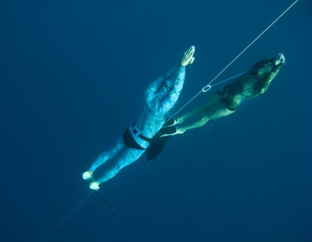 raises: One freediver raises form the depth of Blue Hole, another makes safety dive near the rope Stock Photo