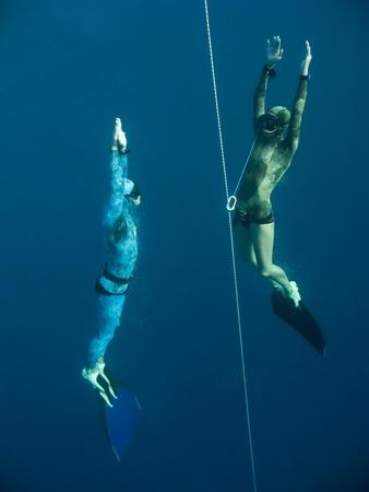 Twee freedivers stijgen van de diepte de buurt van de veiligheidslijn in Blue Hole, Dahab, Egypte