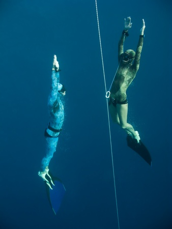 Two freedivers rise from the depth near the safety line in Blue Hole, Dahab, Egypt photo