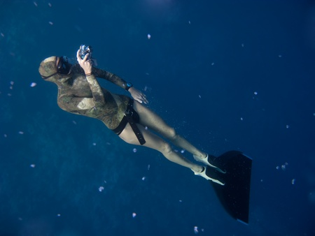 freediver: Freediver with monofin takes photo while standing under the surface