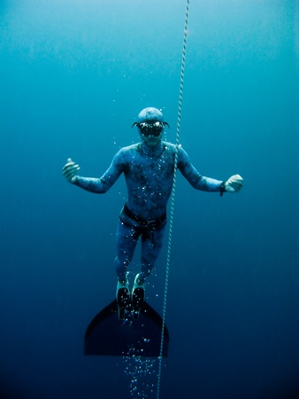 Freediver slowly rises up from the depth of the Blue Hole in Dahab, Egypt