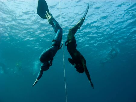 freediver: Two freedivers make simultaneous dive in Bue Hole. Dahab, Egypt
