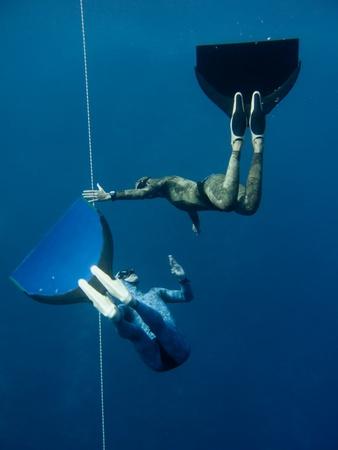 Een freediver stopt zijn beweging, terwijl andere controles vriend het gedrag van