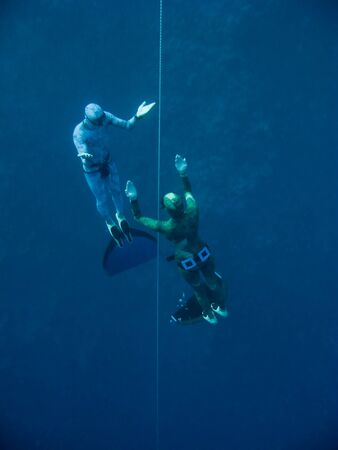 Two freedivers move out from the depth by line near the coral reef in Blue Hole, Dahab, Egypt Stock Photo