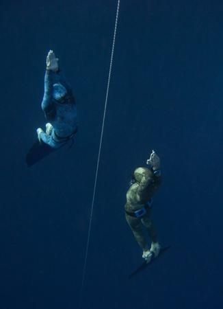 Twee freedivers stijgen van de diepte bij de veiligheidslijn in Blue Hole, Dahab, Egypte