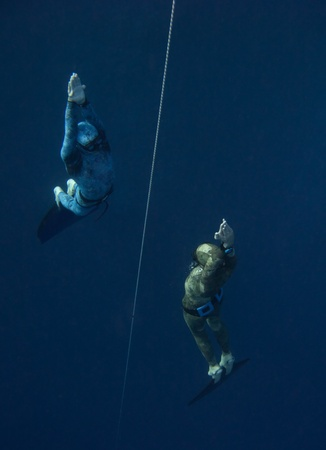 Two freedivers rise from the depth near the safety line in Blue Hole, Dahab, Egypt