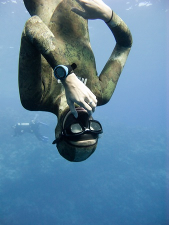 Freediver equalizing pressure while moving down. Meanwhile Blue Hole divers are watching him. Stock Photo