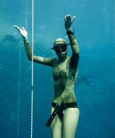 The freediver stands in the depth of Blue Hole, Dahab, while some divers are watching him.  Stock Photo