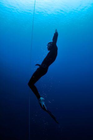 Freediver moves out of the depth of the ocean