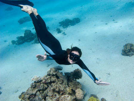 Beautiful girl with monofin looks toward underwater camera near the coral photo