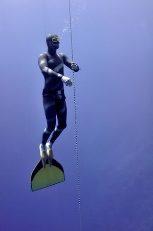 Freediver slowly raises up from the depth by rope