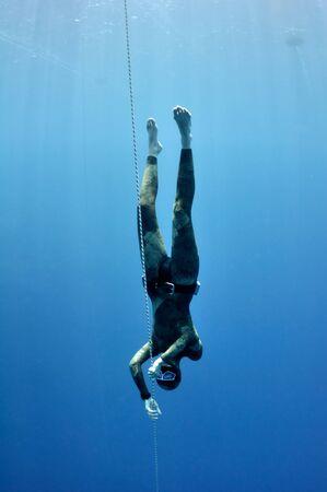 Freediver maakt voorbereiding duiken de buurt van de veiligheidslijn door de schoolslag. Foto toont een deel van freediving training in Blue Hole, Dahab, Egypte