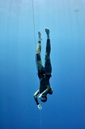 freediver: Freediver makes preparation dive near the safety line by breaststroke. Picture shows a part of freediving training session in Blue Hole, Dahab, Egypt Stock Photo