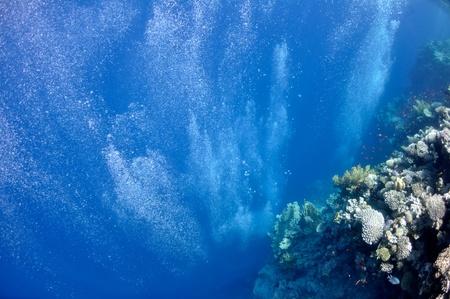 De afbeelding toont onderwater bubbels die van de diepte van blauwe zee verhogen Stockfoto