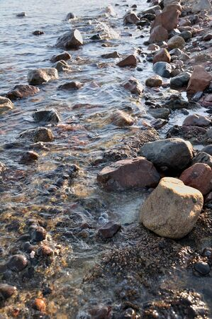 Small stones and rocks at the edge of the sea and in the waves