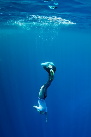 Freediver starts her dive to the sea depth from the surface at the sunlight