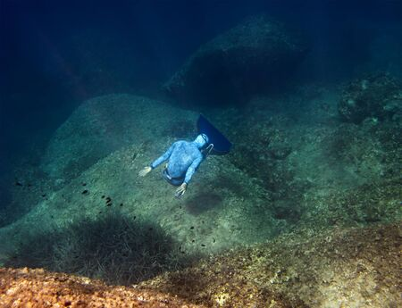 turnover: The freediver makes turnover at the bottom of the sea near underwater rocks