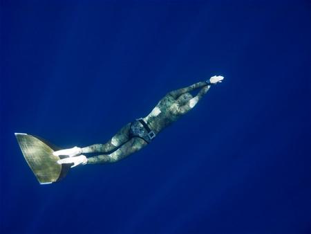 A freediver moves through the ocean depth photo