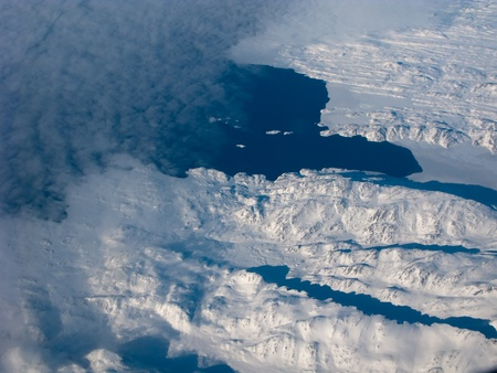 Aerial view of the Greenland coastline with mountain, ocean and clouds