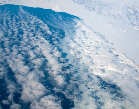 Aerial view of the Greenland coastline with ocean and clouds