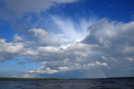 Picture shows saturated and colorful rainbow under beautiful cloud in the sky over lake's surface Stock Photo - 10761505