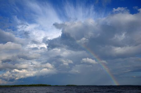 Picture shows saturated and colorful rainbow under beautiful cloud in the sky over lakes surface Stock Photo
