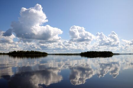 The picture shows typical landscape in the south region of Karelia - blue sky, clouds, big lake looks like a mirror and a lot of distant green islands, trees, stones and rocks