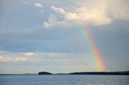 Picture shows saturated and colorful rainbow under single cloud in the sky over lakes surface