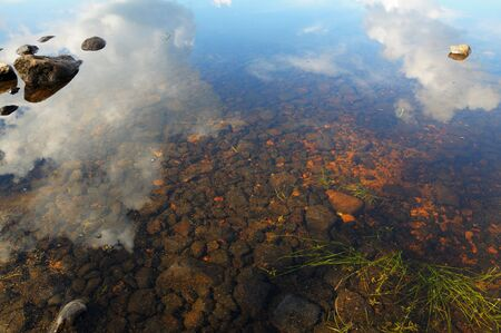The bottom of the lake with a lot of stones and reflected sky