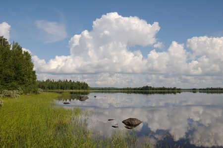 The beautiful picture of Karelian forest at the edge of a lake, and some huge boulder in this lake
