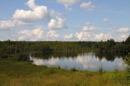 Beautiful lake in a forest under blu sky with cumulus clouds