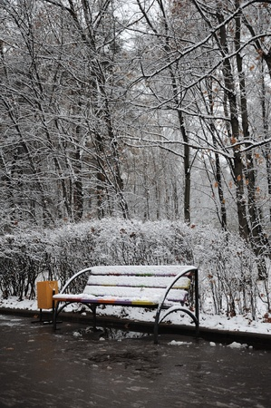 A bench in a winter park, covered by snow.