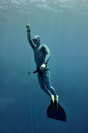 Freediver slowly raises from the depth using safety rope