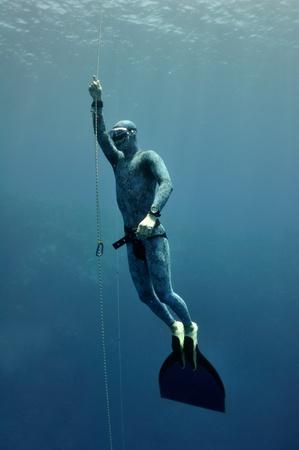 Freediver verhoogt langzaam uit de diepte met behulp van de veiligheid touw Stockfoto
