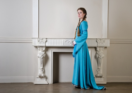 Mooie jonge vrouw in het historische middeleeuwse blauwe jurk vormt in de studio
