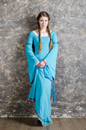 Pretty young woman in historical medieval blue dress poses in studio photo