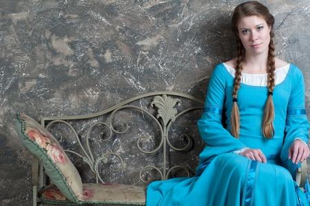 Mooie jonge vrouw in historische middeleeuwse blauwe zit op een banquette in de studio