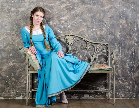 Pretty young woman in historical medieval blue sits on a banquette in studio photo
