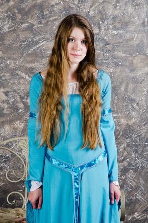 Mooie jonge vrouw in historische middeleeuwse blauwe jurk poses in studio