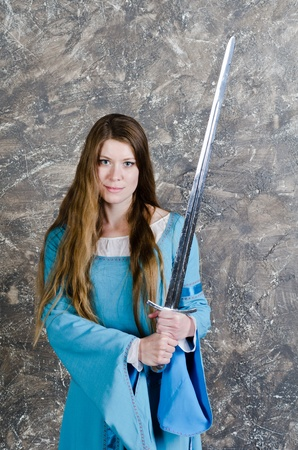 Pretty young woman with long hair in historical medieval blue dress poses in studio with sword Stock Photo - 10921677