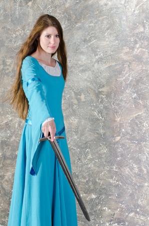 Mooie jonge vrouw met lang haar in historische middeleeuwse blauwe jurk poseert in de studio met zwaard