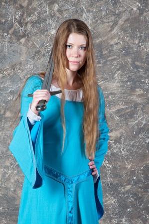 Mooie jonge vrouw met lang haar in de historische middeleeuwse blauwe jurk vormt in de studio met zwaard