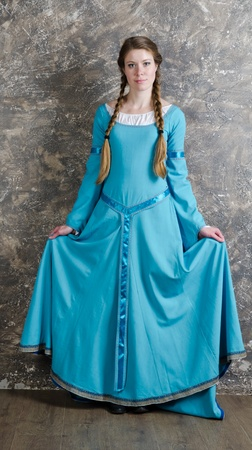 Pretty young woman in historical medieval blue dress poses in studio Stock Photo
