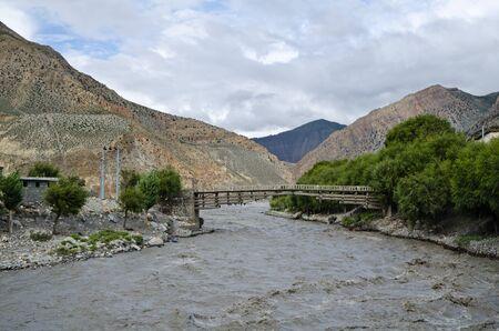 De brug over de snelle, rijke en modderige berg Nepal rivier in de buurt Jomsom dorp Stockfoto