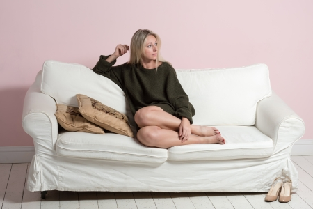 Beautiful young tender woman in sweater is sitting and relaxing on a white sofa photo
